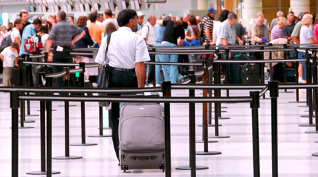 Man with a suitcase joining a line in an airport