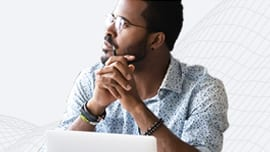 Young man wearing glasses in front of a laptop