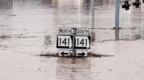 Highway sign in Missouri reading 141 North and South almost completely underwater in a flood
